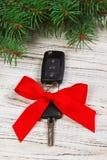 与红色丝带弓的汽车钥匙在白色自然木桌背景 圣诞节或华伦泰` s天礼物或当前抽象conce 免版税图库摄影
