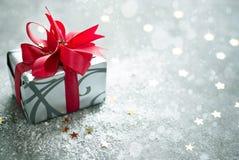 与红色丝带的圣诞节礼物和在灰色背景的金黄星 免版税图库摄影