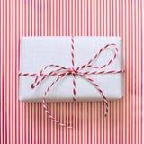 与红色丝带的圣诞节礼物在条纹浮出水面 顶视图 正方形 免版税库存图片