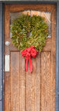 与红色丝带的圣诞节花圈在老木门 免版税图库摄影