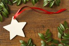 与红色丝带的手工制造,星状空白的圣诞节礼物标记和在土气木背景的自然常青装饰 库存图片
