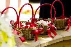 与红色丝带的柳条筐与玫瑰的红色和白色瓣 库存照片