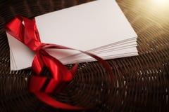 与红色丝带的白色信封在柳条筐 库存图片