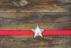 与红色丝带的白色木圣诞节星在木背景 免版税图库摄影