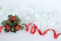 与红色丝带的结霜的白色花圈和绿色叶子,在白色背景的红色礼物党装饰的 免版税库存照片