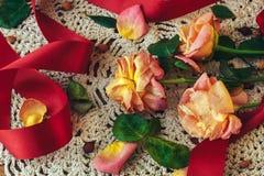 与红色丝带的软绵绵的玫瑰在葡萄酒样式的一块白色鞋带小垫布 图库摄影