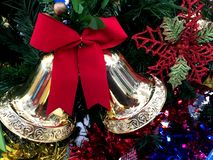 与红色丝带的金铃在圣诞树装饰 图库摄影