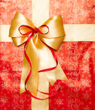与红色丝带的金黄弓在箱子上面 免版税图库摄影