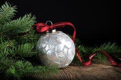 与红色丝带的银色圣诞节装饰品 库存图片