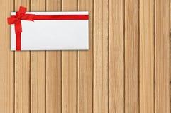 与红色丝带的贺卡在木板条 免版税库存图片