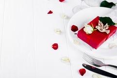 与红色丝带礼物的典雅的假日桌设置 库存图片