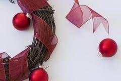 与红色丝带&装饰品的木藤花圈 免版税图库摄影