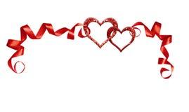与红色丝绸被扭转的丝带和两闪烁心脏的框架 免版税图库摄影