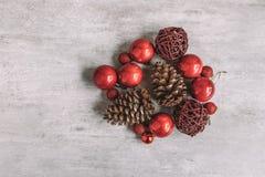与红色中看不中用的物品和杉木锥体的圣诞节构成在木 免版税库存图片