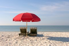 与红色伞的海滩睡椅在白色沙滩 免版税库存照片