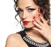 与红色修指甲和嘴唇的美好的时装模特儿 免版税库存照片