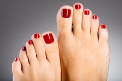 与红色修脚的美好的女性脚 免版税图库摄影