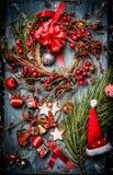 与红色假日装饰的圣诞节花圈和在蓝色土气木背景的圣诞老人帽子 库存图片