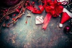 与红色假日装饰,圣诞快乐心脏,莓果的圣诞节背景缠绕和圣诞老人帽子 免版税图库摄影