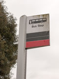 与红色公共汽车的象的一个公共汽车站标志白色和黑和 库存图片