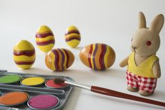 与红色刷子的绘的复活节彩蛋 填充动物玩偶,反对白色背景 免版税库存图片