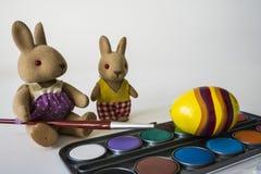 与红色刷子的绘的复活节彩蛋 黄色鸡蛋和填充动物玩偶在白色桌上 免版税库存照片