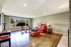 与红色双人沙发和无背长椅的现代客厅内部 库存照片