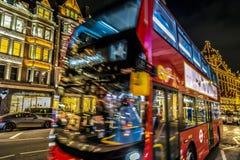 与红色双层公共汽车的夜视图在移动在Harr前面 图库摄影