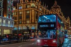 与红色双层公共汽车的夜视图在移动在Harr前面 库存照片