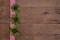 与红色和白色方格的丝带和绿色的木背景 免版税库存照片