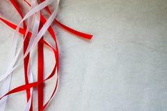 与红色和白色美丽的欢乐丝带的纹理从在浅灰色的背景的一种人为织品 库存图片