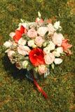 与红色和白花的婚礼花束在草 库存图片