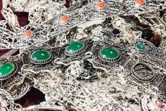 与红色和绿色宝石的银色首饰 免版税库存照片