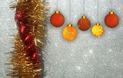 与红色和黄色装饰品的圣诞节背景在银色闪烁背景 免版税库存照片