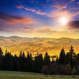 与红色和黄色森林的秋天山坡日落的 免版税库存照片