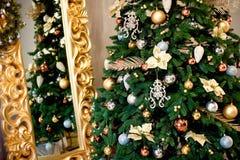 与红色和goldish中看不中用的物品和诗歌选的美丽的装饰的圣诞树,在与壁炉的新年背景中 库存图片