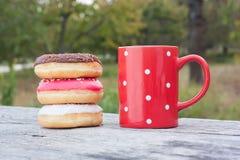 与红色咖啡的五颜六色的油炸圈饼 免版税库存图片