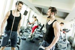 与红色哑铃的肌肉人训练在健身房 库存图片