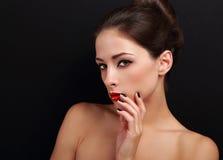 与红色唇膏的性感的挥动的女性模型和手指临近嘴唇看 库存图片