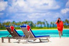 与红色圣诞老人帽子的两个懒人在与绿松石的热带白色海滩浇灌 海滩走的妇女年轻人 免版税图库摄影