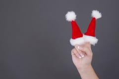 与红色圣诞老人帽子的圣诞节背景在手指 免版税图库摄影