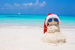 与红色圣诞老人帽子的桑迪雪人在白色 库存照片