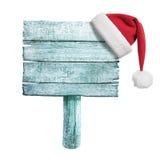 与红色圣诞老人的帽子的冻结的木标志 库存图片