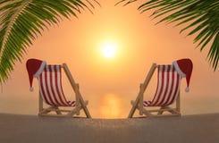 与红色圣诞节圣诞老人帽子的两deckchairs在海洋含沙棕榈日落靠岸 免版税库存照片