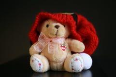 与红色圣诞节帽子的逗人喜爱的玩具熊在深黑色背景 库存照片