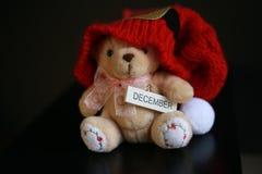 与红色圣诞节帽子的逗人喜爱的玩具熊在深黑色背景 库存图片