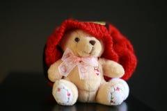 与红色圣诞节帽子的逗人喜爱的玩具熊在深黑色背景 免版税库存图片