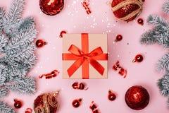 与红色圣诞节球和雪冷杉木的Giftbox在桃红色淡色背景 免版税库存图片