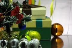与红色圣诞节球的逗人喜爱的绿色礼物在绿色抽象轻的背景 库存照片
