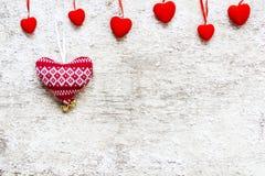 与红色天鹅绒心脏和被编织的心脏的情人节背景 库存照片